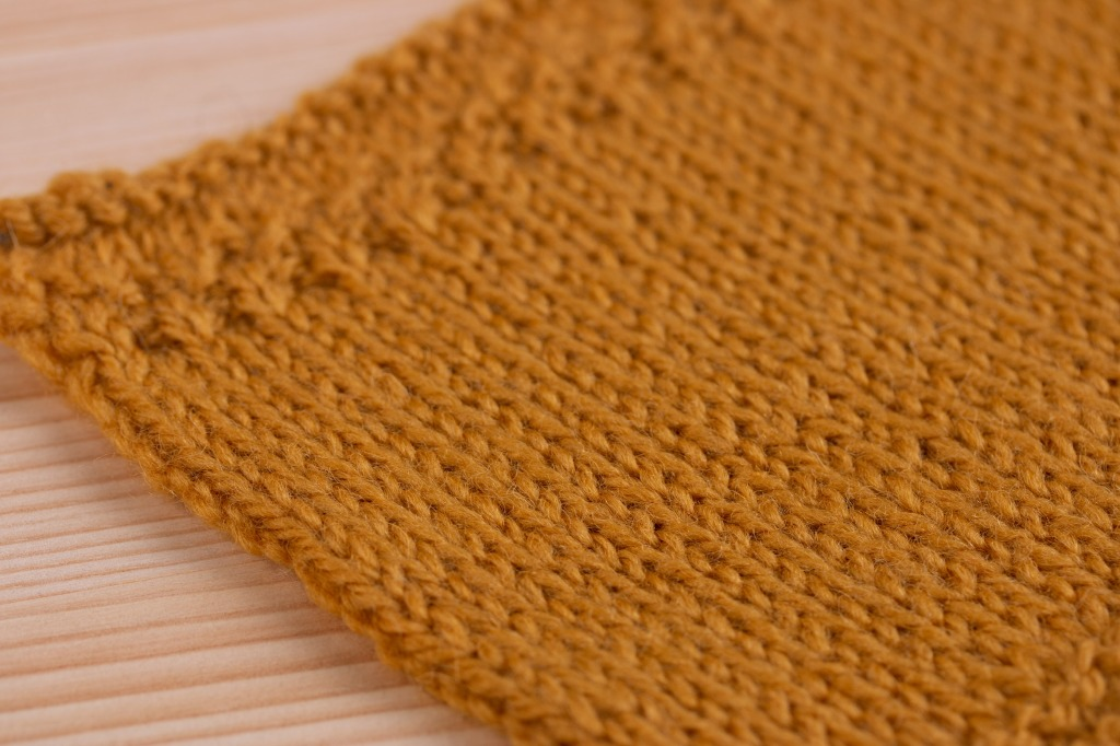 Stocking stitch sampler knitted in yellow 100% wool yarn. My very first piece of knitting.