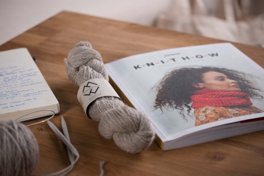Image of journal, knitting needles, Haar (grey) Buachaille wool yarn and Pomp Pom Knithow Book.