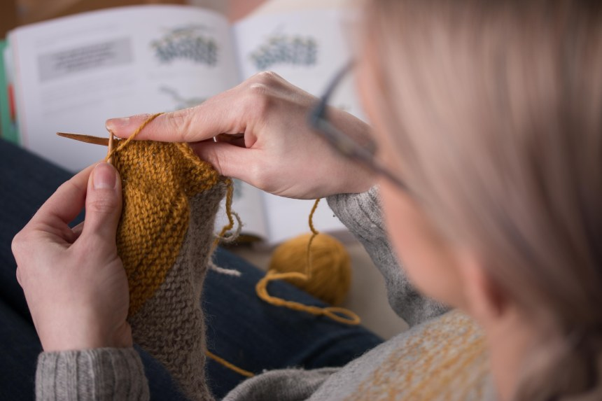 Jane Hunter sits on the couch knitting with bamboo needles, yellow wool yarn and a learn to knit book.