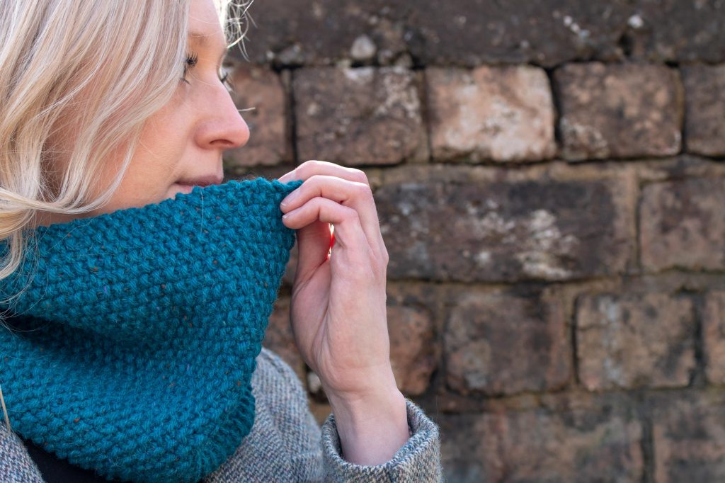 Model wearing blue hand knit cowl and Harris Tweed Jacket